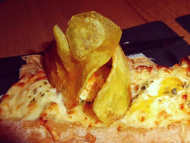 Pan de cristal a los cuatro quesos con huevo de codorniz.
